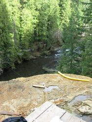 looking down mound at river and siphon hose (Umpqua)