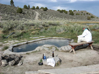 Andy sitting on bench next to pool (little hot creek)