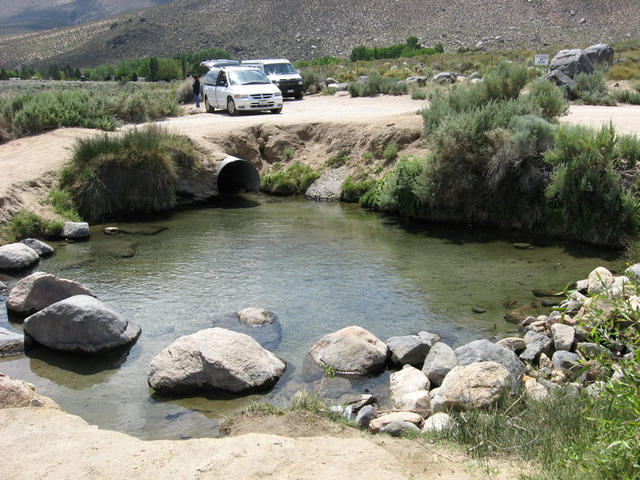 A middle pool with vans in the parking area in background (Keough Hot Ditch)